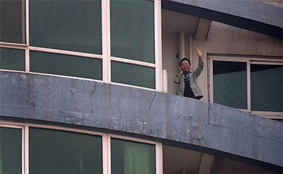 Tibetan blogger Woeser waves from the balcony of her home in Beijing on March 8. She was named an International Woman of Courage by U.S. Secretary of State John Kerry, but rather than being allowed to accept it, she was placed under house arrest. (Reuters/Petar Kujundzic)