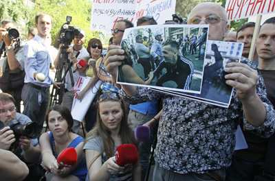 Journalists in Kiev protest police officers' failure to intervene in an assault against two reporters. A demonstrator holds a photo of a man said to have been among the assailants. (Reuters/Gleb Garanich)