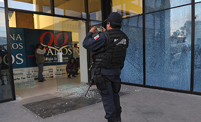 A Mexican police officer photographs the main entrance of El Siglo de Torreón after an attack on the offices. (AFP/El Siglo de Torreón)