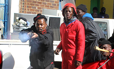 A security officer fires rubber bullets at Star photographer Motshwari Mofokeng. (The Star)