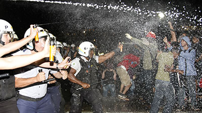 At least 25 journalists have been attacked during clashes between demonstrators and police in Brazil. Here, police in Brasilia spray protesters with pepper gas during a demonstration. (AFP/Beto Barata)
