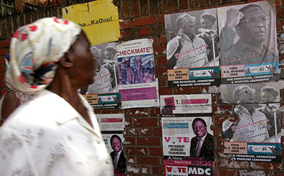 A Zimbabwean citizen passes election posters advertising election candidates. At least four journalists have been attacked in the lead-up to the elections in July. (AFP/Alexander Joe)