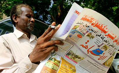 A Sudanese man reads Al-Intibaha, a prominent daily that has been banned by the NISS. (AFP/Ashraf Shazly)