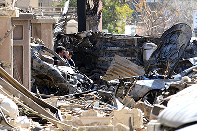 A journalist photographs damage from twin bomb attacks in Damascus. (AFP/Louai Beshara)