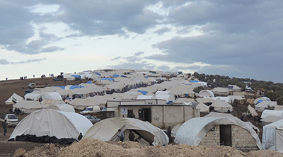سوريون لجأوا إلى مخيم لاجئين قرب الحدود التركية. (رويترز/ محمد نجدت قدور/ شبكة شام الإخبارية)