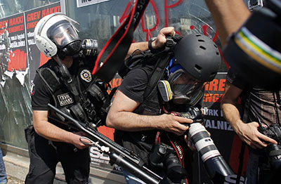 A police officer clashes with a photographer in Taksim Square. (Reuters/Murad Sezer)