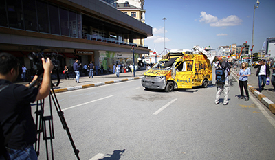 A TV crew films near a vandalized news vehicle in Taksim Square. (Reuters/Stoyan Nenov)