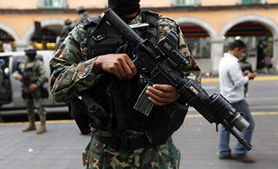 Several journalists, including Miguel Angel López, have fled Veracruz state fearing reprisal from cartels, gangs, or the government. Here, a soldier is seen standing guard in downtown Veracruz. (Reuters/Edgard Garrido)