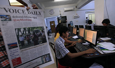A journalist holds a copy of The Voice at a newsroom in Rangoon. (Reuters/Soe Zeya Tun)