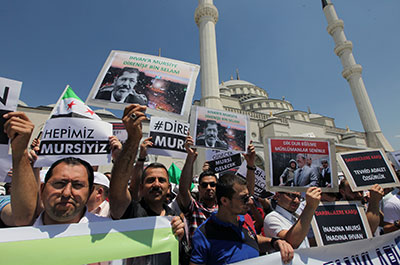 """Turks hold posters reading """"We are all Morsi"""" and """"Resist, Morsi"""" outside Kocatepe Mosque in Ankara, Turkey, on July 5. (AP/Burhan Ozbilici)"""
