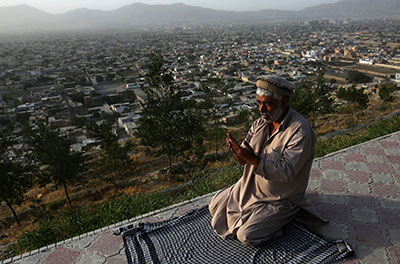 A man offers evening prayers on a hilltop overlooking Kabul on Wednesday. As the devout mark the holy month of Ramadan, Afghanistan's warlords and powerbrokers must decide on a successor to President Hamid Karzai. (Reuters/Omar Sobhani)