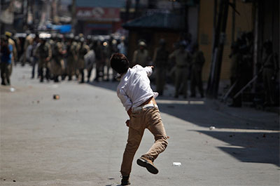 A Kashmiri youth throws a piece of brick at Indian police during a protest in Srinagar on July 18. Indian paramilitary soldiers fired at protesters in the region last week, killing four. (Reuters/Danish Ismail)