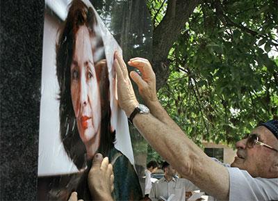Люди вешают плакат с изображением Натальи Эстемировой на монумент погибшим журналистам в г. Грозном, чеченской столице на юге России, 15 июля 2011 года. AP/Муса Садуллаев