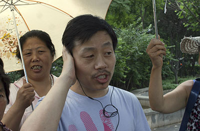 Du Bin speaks on his phone after being released conditionally from jail. (AP/Hu Jia)