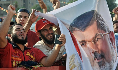 Journalists report being harassed, censored, and attacked amid clashes between supporters and opponents of ousted President Morsi. Here, Morsi supporters hold up his portrait and shout slogans. (AFP/Fayez Nureldine)
