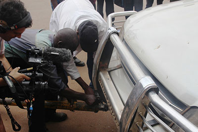 Moments before his arrest, Taylor Krauss films damage to opposition leader Kizza Besigye's car by police. (Chimpreports)