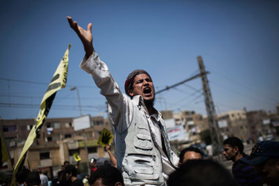 A supporter of Egypt's ousted President Mohamed Morsi chants slogans against the military Friday in Cairo. (AP/Manu Brabo)