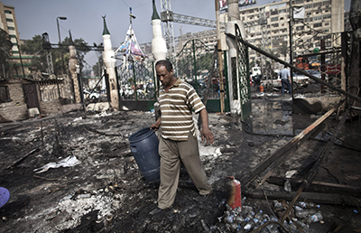 A Egyptian citizen walks through the debris at Rabaa Al-Adawiya square. (AFP/Mahmoud Khaled)