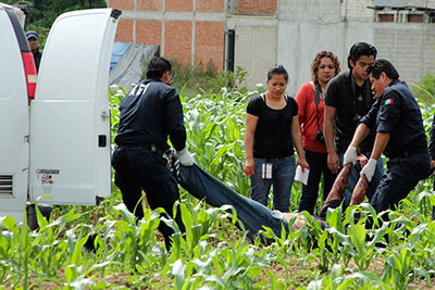 Police remove the body of Alberto López Bello, a crime reporter, from a crime scene in Oaxaca on July 17. (Reuters/Jorge Luis Plata)