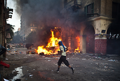 A man runs past a burning vehicle in Ramses Square. (AFP/Virginie Nguyen Hoang)