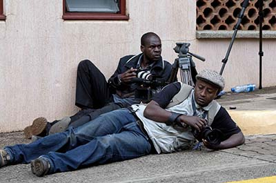 Two photographers take cover outside the Westgate Mall. (AP/Sayyid Azim)