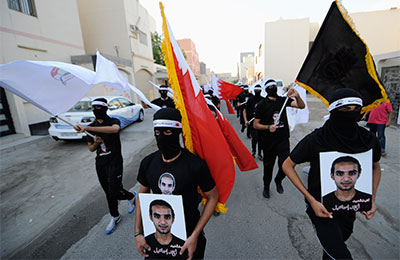 Masked protesters carry portraits of Ahmed Ismail Hassan at a demonstration in Salmabad village, south of Manama, Bahrain, April 10, 2013. (Reuters)