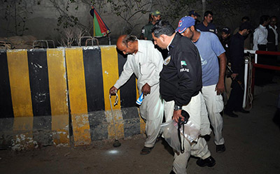 Security officials examine the scene of Monday's attack on Express Media Group in Karachi. (AFP)