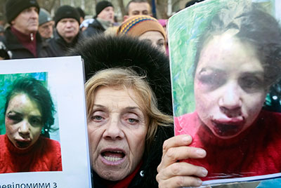 A protester holds pictures of Tetyana Chornovol, who was beaten and left in a ditch hours after publishing an article on the assets of a top government official. (Reuters/Gleb Garanich)