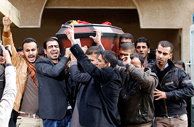 Mourners carry the coffin of Yasser Faisal al-Jumaili, who was killed on assignment in Syria, at his funeral in Falluja, Iraq, on December 8. (Reuters/Thaier Al-Sudani)