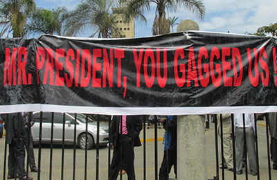 A banner tied to the gates of Parliament protests a media bill under review. (CPJ/Tom Rhodes)