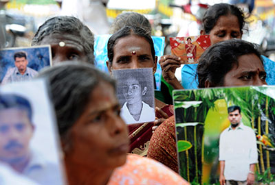 Sri Lankan Tamils hold pictures of family members who disappeared during the war between government forces and the Liberation Tigers of Tamil Eelam at a protest in Jaffna on November 15. (Reuters)