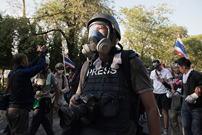 A photographer wears a gas mask to cover the anti-government protest in Bangkok. (AFP/Nicolas Asfouri)