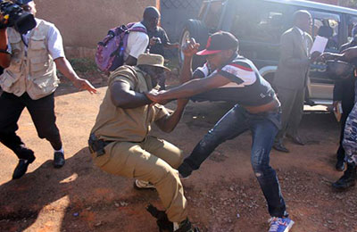 Police attempt to arrest a supporter of Erias Lukwago outside his home on December 2. (Monitor)