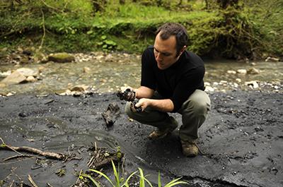 Сурен Газарян исследует чёрное вещество найденное в глине недалеко от Сочи. (AFP/Mikhail Mordasov)