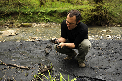 Suren Gazarian examines a black substance in the mud near Sochi. (AFP/Mikhail Mordasov)