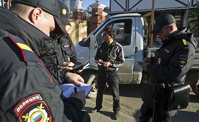 Сотрудники полиции проверяют водительское удостоверение на посте регулирования движения. (Reuters/Maxim Shemetov)