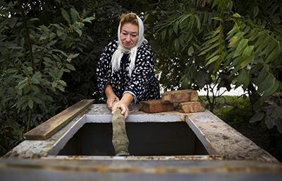 Женщина берёт недельный рацион воды в Сочи. С момента начала олимпийской стройки многие колодцы в Сочи опустели. (Reuters/Thomas Peter)