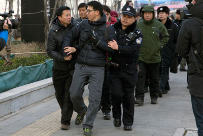 Chinese policemen manhandle a foreign photographer outside the trial of Xu Zhiyong, founder of the New Citizens movement, in Beijing on January 26. (AP/Andy Wong)