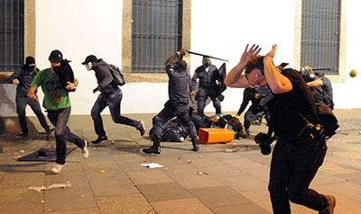 Manifestantes chocan con la policía antidisturbios el 17 de junio de 2013 durante una protesta en Río de Janeiro contra de los miles de millones de dólares gastados en la preparación para el Mundial de fútbol y contra de un aumento en las tarifas de transporte público. ( AFP / Tasso Marcelo )