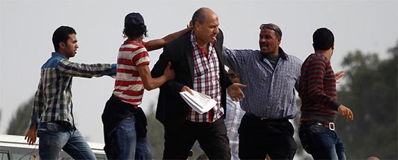 Partidários da Irmandade Muçulmana tentam empurrar um jornalista, ao centro, para longe da academia de polícia onde o presidente deposto Mohamed Morsi foi a julgamento, nos arredores de Cairo, em 4 de novembro de 2013. Talvez em nenhum lugar a liberdade de imprensa teve um declínio de forma mais dramática em 2013 do que no polarizado Egito. (Reuters/Amr Abdallah Dalsh).