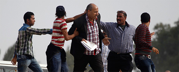 Supporters of the Muslim Brotherhood try to push a journalist, center, away from the police academy where ousted President Mohamed Morsi was on trial on the outskirts of Cairo, November 4, 2013. Perhaps nowhere did press freedom decline more dramatically in 2013 than in polarized Egypt. (Reuters/Amr Abdallah Dalsh)
