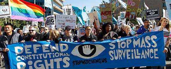 Демонстранты маршируют недалеко от здания конгресса США в Вашингтоне на акции протеста 26 октября 2013 требуя от законодателей провести расследования программ массовой слежки, проводимой Агентством национальной безопасности. (AP/Jose Luis Magana)
