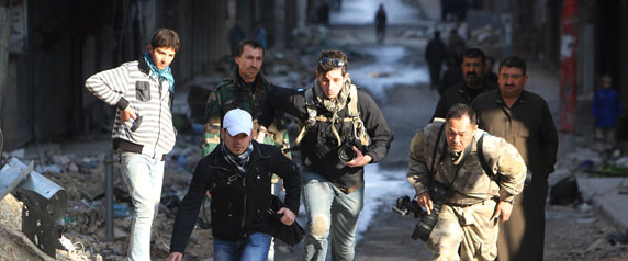 Journalists Bryn Karcha, center, of Canada, and Toshifumi Fujimoto, right, of Japan, run for cover with an unidentified fixer in Aleppo's district of Salaheddine on December 29, 2012. (Reuters/Muzaffar Salman)