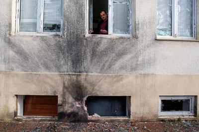 Vijesti Editor-in-Chief Mihailo Jovovic looks through a window damaged in a bomb blast at the newspaper's offices in Podgorica on December 27, 2013. (Reuters/Stevo Vasiljevic)