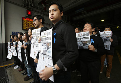 Journalists from Ming Pao hold up front pages of the paper to protest an attack on their former chief editor, Kevin Lau Chun-to. (Reuters/Bobby Yip)