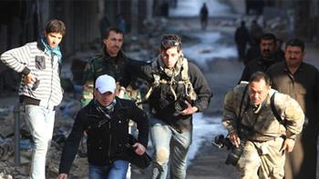 الصحفيان براين كرشة من كندا في الوسط وطشفمي فوجيموتو من اليابان على اليمين يهربان من الخطر مع مساعد صحفى مجهول الهوية في حي صلاح الدين في حلب  في29 ديسمبر2012. رويترز  مظفر سلمان