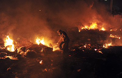 A protester is seen near a barricade of flames between police and demonstrators in Kiev. (AFP/Louisa Gouliamaki)