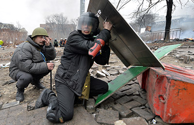 Protesters take cover amid clashes with police in Kiev on February 20. (AFP/Sergei Supinsky)