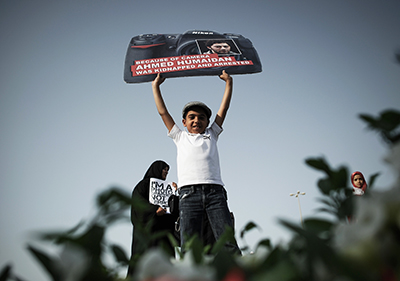 A Bahraini boy holds a sign protesting the December 2012 arrest of freelance photographer Ahmed Humaidan. (AFP/Mohammed al-Shaikh)