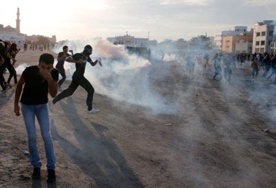 Anti-government protesters take cover from teargas fired by riot police in the village of Daih on March 3. (Reuters/Hamad I Mohammed)